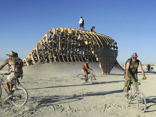 Burning Man participants ride bikes and climb a sculpture on the Black Rock Desert playa last year. Grassroots Books will screen an informational documentary about Burner culture tonight.