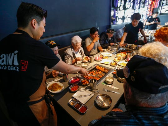 Cosmo Kwon, left, co-owner of Bawi, grills a batch of spicy pork during the restaurant's special grand-opening event for Korean War veterans held during 2018.