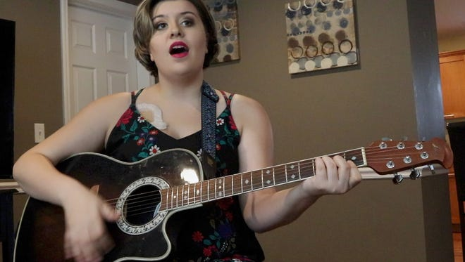McKenzy Hupke plays her guitar and sings in the livingroom of her Lacey Township home.