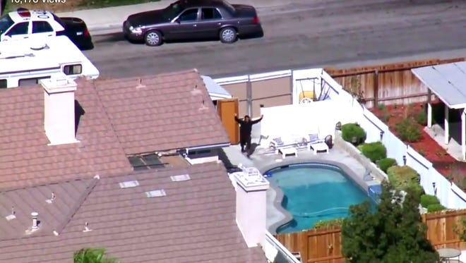 This still frame from video provided by KTTV-TV shows a man with his hands up in the backyard of a home as authorities search for a gunman who shot and killed Los Angeles County Sheriff Sgt. Steve Owen, in Lancaster, Calif., Oct. 5, 2016.