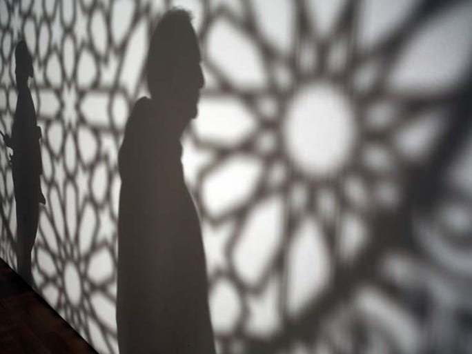 """Silhouettes are people taking in the 3-D piece of Anila Quayyum Agha's """"Intersections"""" at the Grand Rapids Art Museum Tuesday, Sept. 30, 2014 during artprize 2014."""