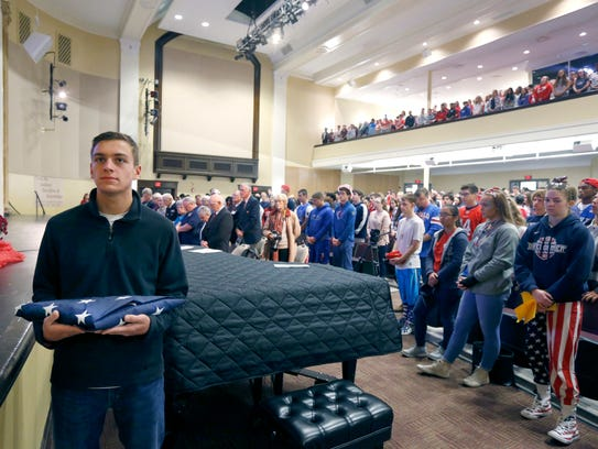 Aquinas senior Brendan Humphries holds the American flag during a ceremony at Aquinas Institute to mark the 50th anniversary of Don Holleder's death in Vietnam. The flag was later handed to Holleder's daughter Katie Holleder Fellows, who carried it outside to be raised on the school's flag pole.