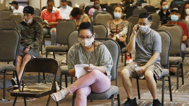 People wait to speak with representatives from the Oklahoma Employment Security Commission about unemployment claims in Midwest City, Okla., on July 9.