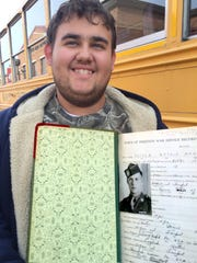 Jeremy Teeter holds a ledger book with the War Service Record of a relative, Sgt. Arthur Teeter.