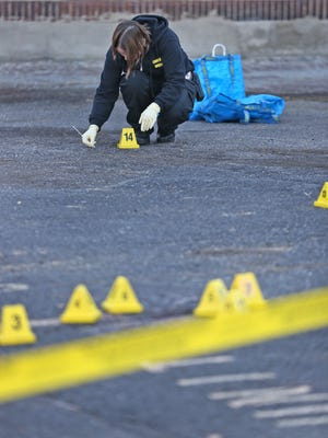 IMPD crime scene specialist Melissa Bitters gathers evidence at the scene of an early morning assault in the 200 block of E. 9th Street, Wednesday, November 4, 2015.  The victim later died.