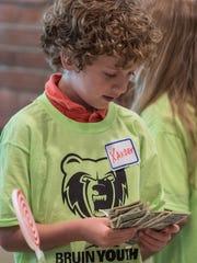 Xander Yoder counts money at a young entrepreneurs