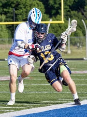 Hartland's Jake Gallaher (13) is defended by Detroit
