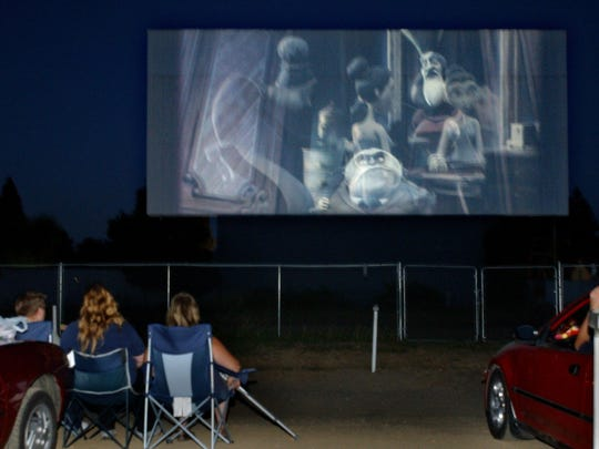 """People watch the movie """"Charlie and the Chocolate Factory"""" at the Motor Vu Drive-In Theater on Aug. 3, 2005. The Dallas Motor-Vu Drive-In closed last year after being in business since 1953."""