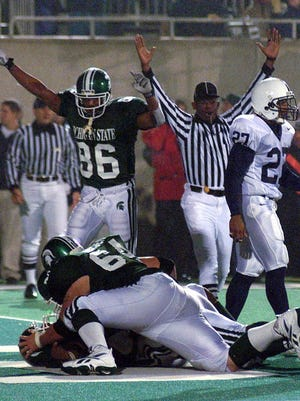 MSU running back T. J. Duckett, below, is congratulated by teammates after scoring the winning touchdown against Penn State in 1999  as Gari Scott (86) looks on.