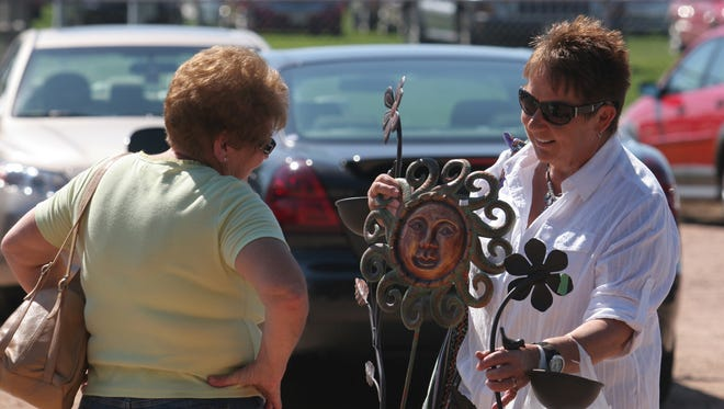 Marcia Stanczak of Wausau, right, shows off one of her purchases to friend Judy Schlueter of Merrill in a parking lot at Marathon Park, Saturday, September 10, 2011,  during the Artrageous Festival of Arts in Wausau.