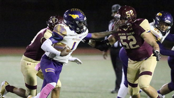 Burges running back Quan Mcneil, 1, stiff-arms Gabriel Hermosillo, 52, of Andress Friday night.