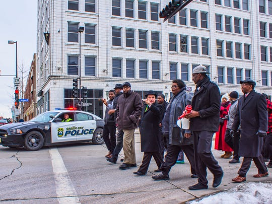 Marchers take to the streets of downtown Green Bay on Monday to mark Martin Luther King Jr. Day .