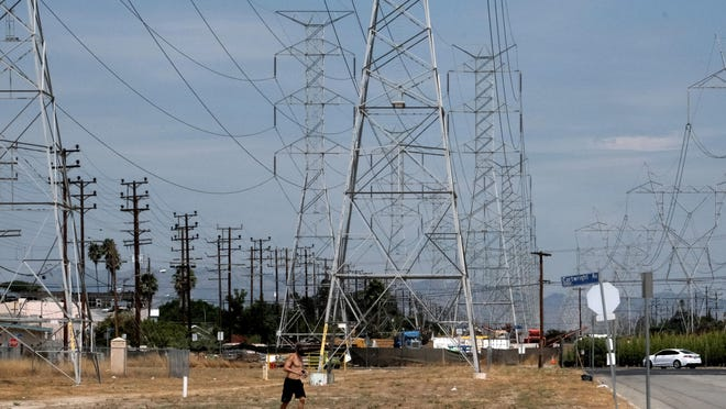 A jogger runs in extreme heat under high tension electrical lines in the North Hollywood section of Los Angeles on Saturday. California has ordered rolling power outages for the first time since 2001 as a statewide heat wave strained its electrical system.