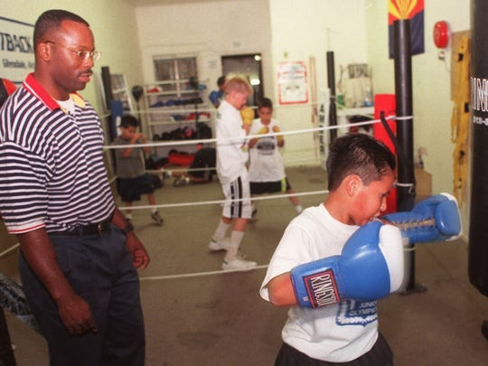 Glendale police Officer Andre Anderson, 34, works in 1999 with Roy Guizar, 10, at the Outback Gym in Glendale. Anderson, who was once a professional boxer,  volunteered at the gym at least once a week.