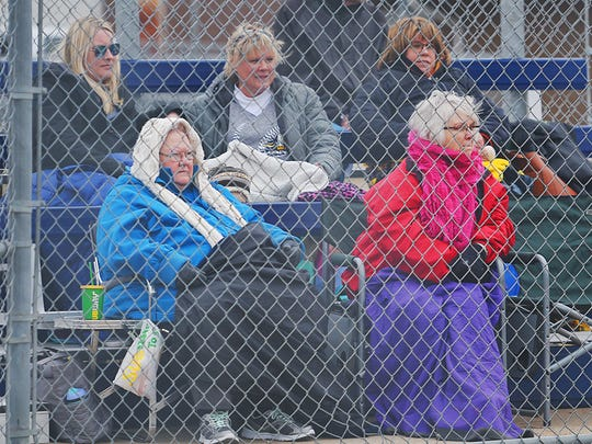 Augustana softball fans bundle up in jackets and blankets