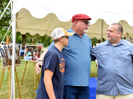 "York native and Arizona Cardinals coach Bruce Arians, center, speaks with William Penn head football coach Russ Stoner, right, at a York City Parks Conservancy event Saturday, June 17, 2017, in York's Memorial Park. Arians will serve as the honorary chairman of the Conservancy, a nonprofit that will be ""a mechanism to endow the ongoing investment of our York City Parks,"" according to Tony Campisi, Glatfleter Insurance Group president/CEO and Conservancy capital campaign chair. ""This is in perpetuity. This is designed to be forever."""