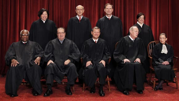 U.S. Supreme Court justices pose for a group photo at the Supreme Court in Washington.
