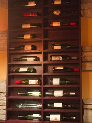 A display of wine bottles is mounted on the wall of