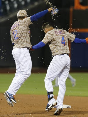 New York Mets Juan Lagares sprays teammate Wilmer Flores (4) with sunflower seeds after Flores hit a game-winning, RBIn single in the Mets 4-3 walk-off victory over the Toronto Blue Jays in a baseball game in New York, Monday, June 15, 2015. The Mets win ended the Blue Jays ten-game winning streak. (AP Photo/Kathy Willens)