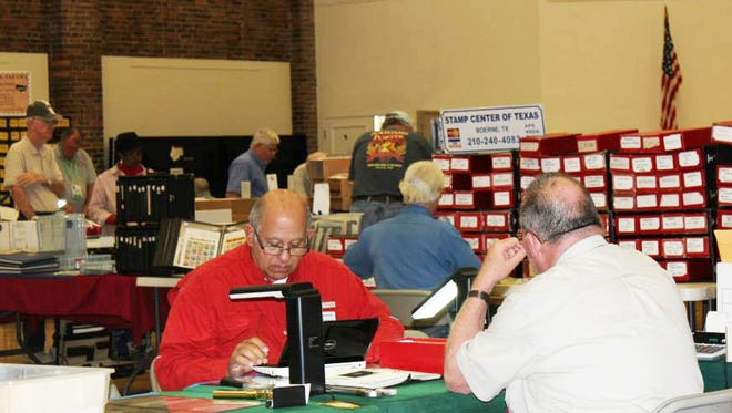 Dr. Mike (in red) is seen working with a stamp dealer at a recent philatelic exhibition in Tallahassee.