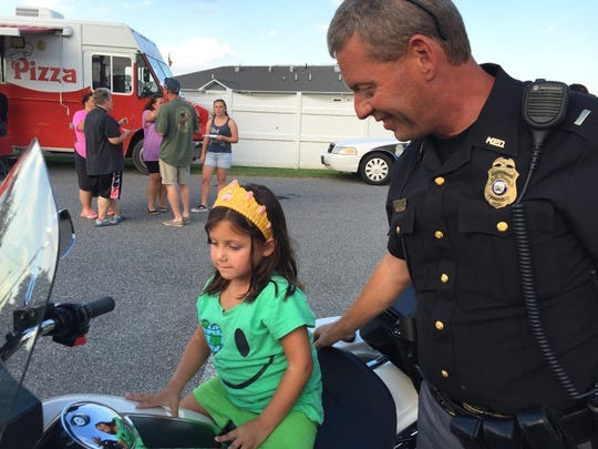 Olivia Cylinder, 5, of Milford sits on the seat of a police motorcycle next to Milford Police Department Lt. Edward Huey on Tuesday during a National Night Out event.