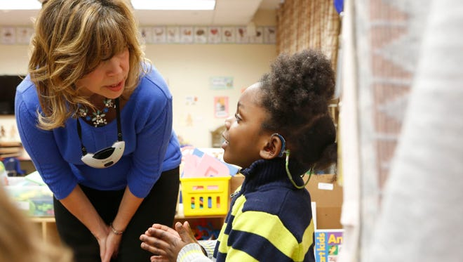 Rosemarie Lynch, teacher in the Auditory Oral preschool classroom at the New York School for the Deaf in White Plains,  talks to 4-year-old Jaden Dossous. Lynch wears a microphone around her neck, which connects directly to an FM system, so each of her students can hear her clearly.