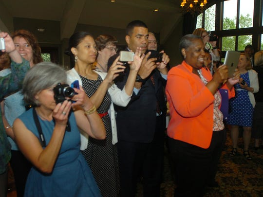 Excited parents and friends snap group photos during the Superintendent's Award of Excellence celebration.