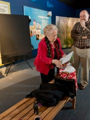 Maria Davis, Spanish consul, left, and Robert Overton, West Florida Historic Preservation, Inc., CEO, right, review plans for the unveiling of a new painting of General Bernardo de Galvez that will go on public display at the T.T. Wentwoth Museum.