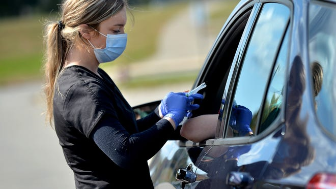 Hailey Derosa, a medical assistant at AFC Urgent Care in Marlborough, administers the flu vaccine at a drive-through flu clinic at Hudson High School Saturday, Oct. 3.
