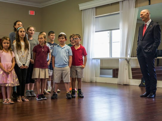 Governor Rick Scott watches as a group of children
