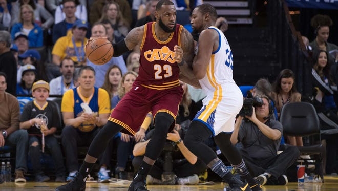 Cleveland Cavaliers forward LeBron James (23) dribbles the basketball against Golden State Warriors forward Kevin Durant (35) during the third quarter at Oracle Arena. The Warriors defeated the Cavaliers 126-91.