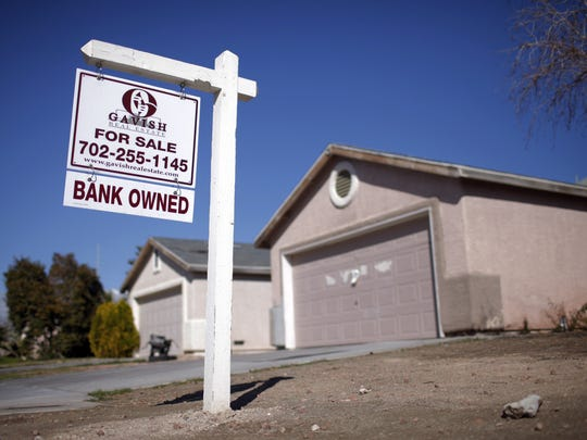 A for sale sign stands outside a bank-owned home in North Las Vegas in 2009. Homes like this one can become targets of squatters.