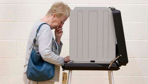 A woman votes in 2012.