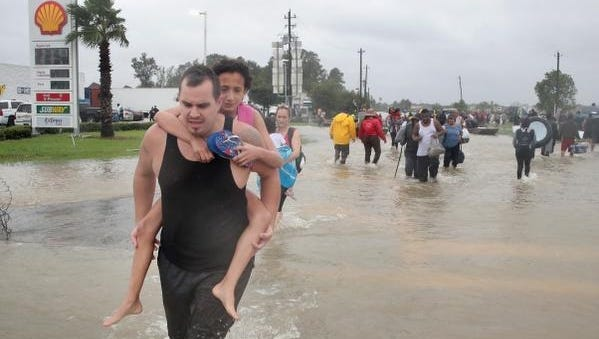 People make their way out of a flooded neighborhood after it was inundated with rain water, remnants of Hurricane Harvey.