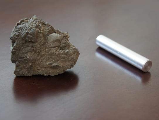 A piece of dolomite rock at left, next to a rod of