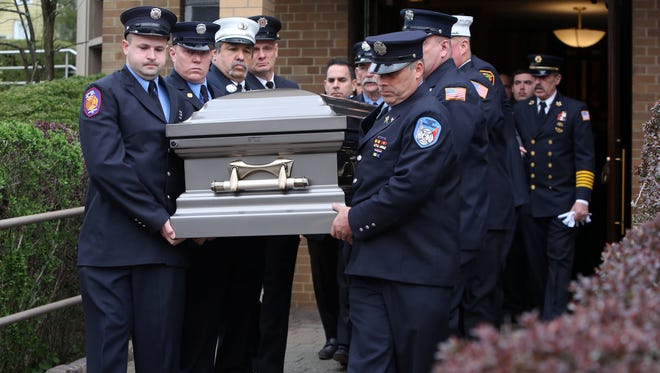 """Firefighters carry the casket of Fairview firefighter Robert """"Bubba Bert"""" Mentrasti, who died of 9/11 related cancer, after his funeral at Sacred Heart Church in Hartsdale April 19, 2017."""