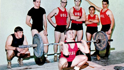 Jimmy Reinhardt demonstrates a squat clean for members of the USL weightlifting team, which won the national championship for the second consecutive year in 1966. It was the third time in the previous four years the squad claimed the title. Watching him were, from left, John Stelly, John Arceneaux, Warren Perrin, George Weatherford, Randy Peloquin and Eddie Ortego.