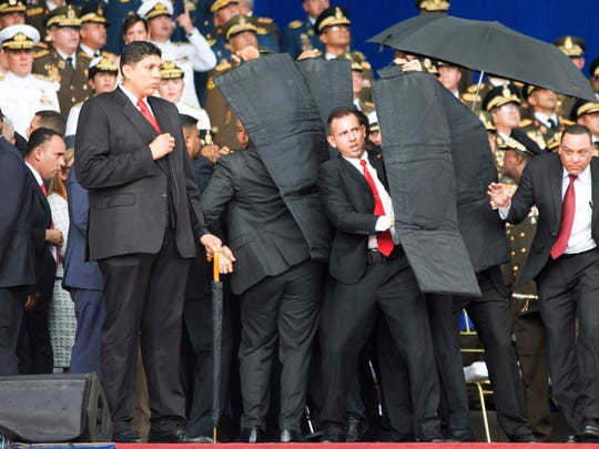 In this photo released by China's Xinhua News Agency, security personnel surround Venezuela's President Nicolas Maduro after a reported drone attack as he was giving a speech in Caracas, Venezuela, on Saturday.