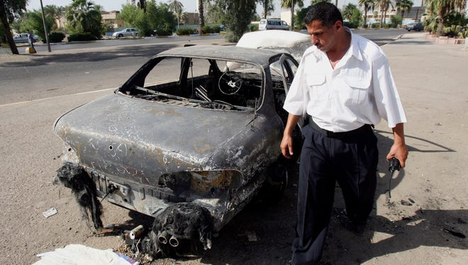 An Iraqi traffic policeman inspects a car destroyed by a Blackwater private contractor detail during the Nisoor Square attacks in September, 2007.
