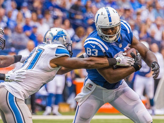 Indianapolis Colts tight end Dwayne Allen (83) catches the ball while Detroit Lions defensive back Rafael Bush (31) tackles him in the second quarter of a 2016 game at Lucas Oil Stadium.