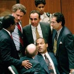"""In this Sept. 28, 1995 file photo, O.J. Simpson is surrounded by his """"Dream Team"""" defense attorneys from left, Johnnie L. Cochran Jr., Peter Neufeld, Robert Shapiro, Robert Kardashian, and Robert Blasier, seated at left, at the close of defense arguments in Los Angeles."""