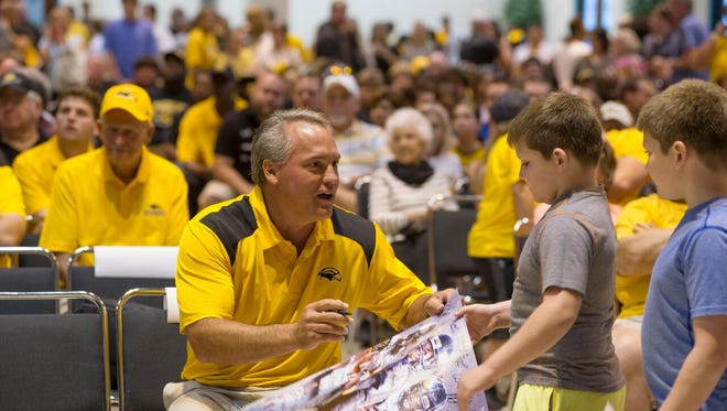 USM Head Football Coach Jay Hopson signs a poster for a young fan at one of the Big Three parties across the state.