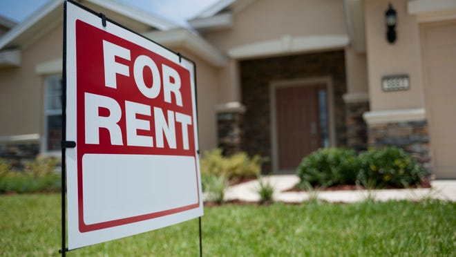 """A rental home with a """"for rent"""" sign in the lawn."""
