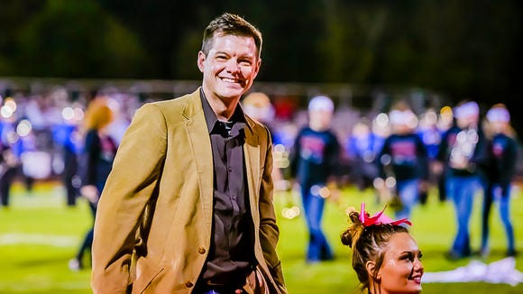 MLB umpire D.J. Reyburn ,left, smiles as he is introduced to the crowd at halftime of the St. Johns/DeWitt football game.  Reyburn, a DeWitt alum, was inducted into the DeWitt Hall of Fame.
