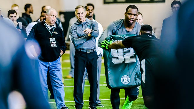 MSU coach Mark Dantonio points during a defensive line drill while talking to Balimore Ravens defensive coordinator Dean Pees, left, during MSU's Pro Day on March 16. Pees is a former Spartan assistant coach.