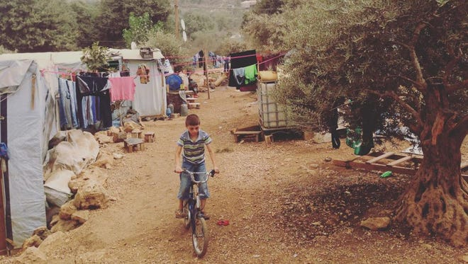 A young boy rides his bicycle at an informal camp for Syrian refugees in Ketermaya, Lebanon.