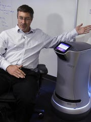 Steve Cousins, CEO of Savioke, talks while sitting next to a Relay robot at company headquarters in San Jose, Calif. Tech companies insist their products will largely assist, and not displace, workers. Savioke makes the 3-foot-tall Relay robots that deliver room service at hotels where only one person might be on duty at night, allowing the clerk to stay at the front desk. (AP Photo/Ben Margot)