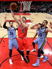 Chicago Bulls' Zach LaVine, center, scores between Memphis Grizzlies' Dillon Brooks, left,  and Marc Gasol, right, during the first half of an NBA basketball game Wednesday, March 7, 2018, in Chicago. (AP Photo/Charles Rex Arbogast)