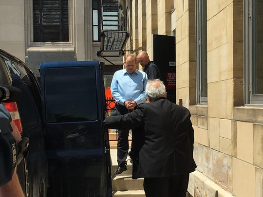 Former Clinton Township trustee Dean Reynolds is led to a van outside federal court in Port Huron after being convicted of bribery and bribery conspiracy charges on Thursday, June 21, 2018.