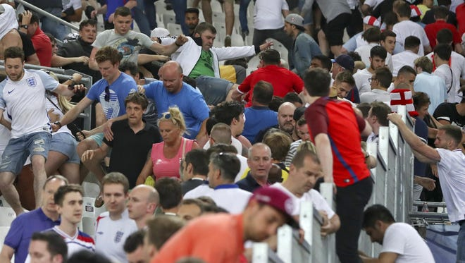 Spectators run on the stands as clashes break out after the match.